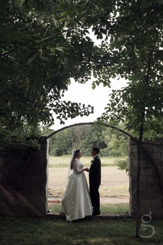 the bride and groom with the remains of the fallen barn