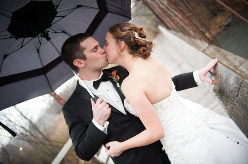 kissing in the rain under a black umbrella in wedding attire.