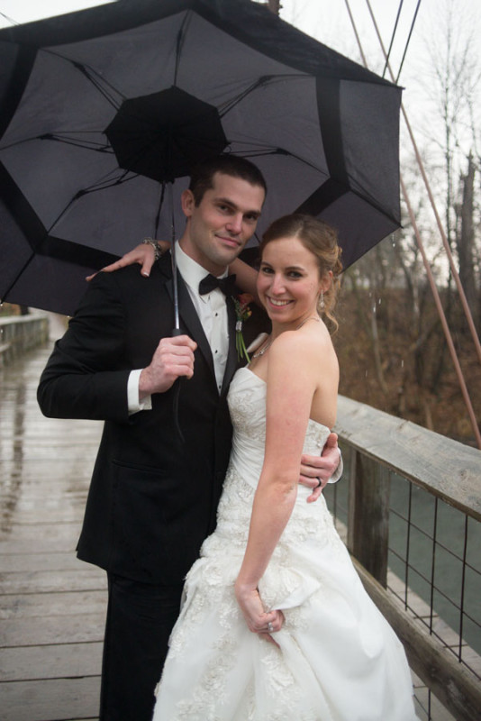 bridal portraits in the pouring rain on an old wooden bridge.