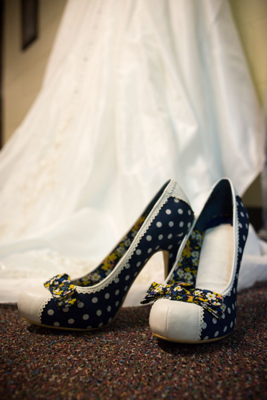 The bride's amazing blue and white polka dotted shoes that were picked out by the groom.