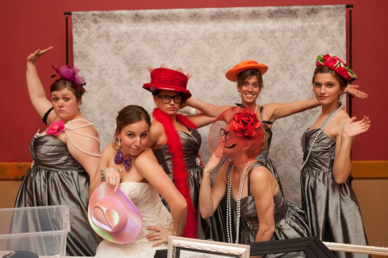 the bridesmaids getting in on some photobooth action with props and hats