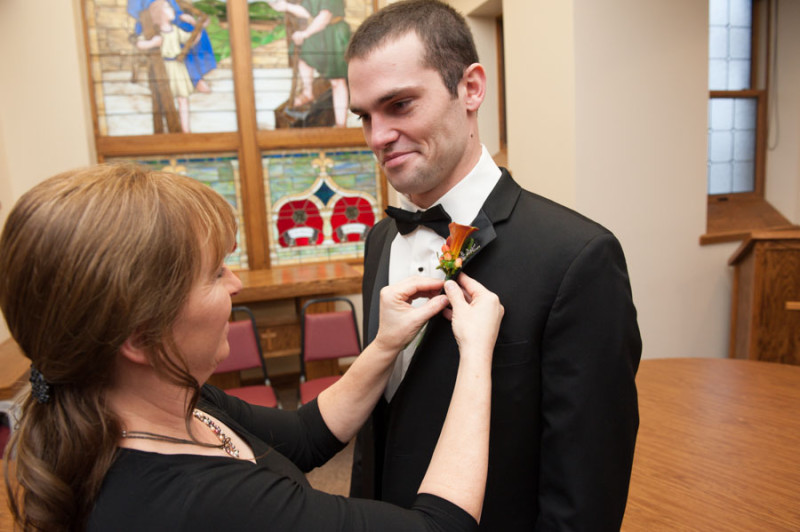 The groom getting his boutonnier pinned on from his mom, flowers from Amber Moon in Baraboo.