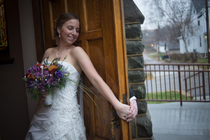 Megan holding David's hand against the church's thick wooden door.