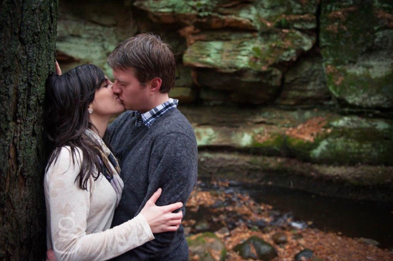 rainy day kiss in front of green coated rocks