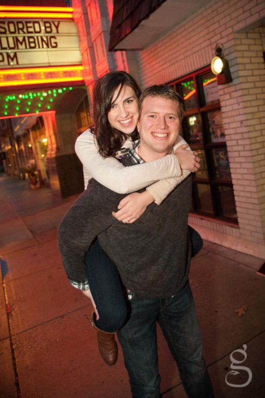 piggy back engagement in front of the theatre