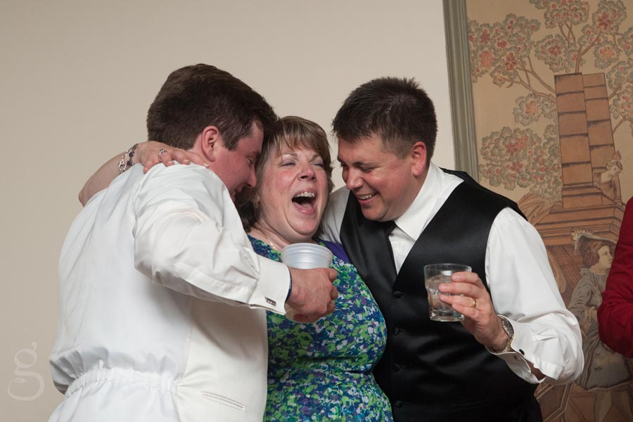 Mother of the groom laughing at her boys.