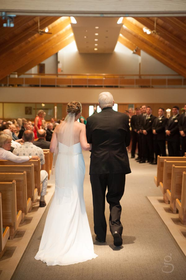back view of the bride and her father walking down the aisle