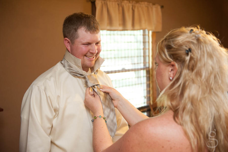 handsome groom getting his tie tied on.