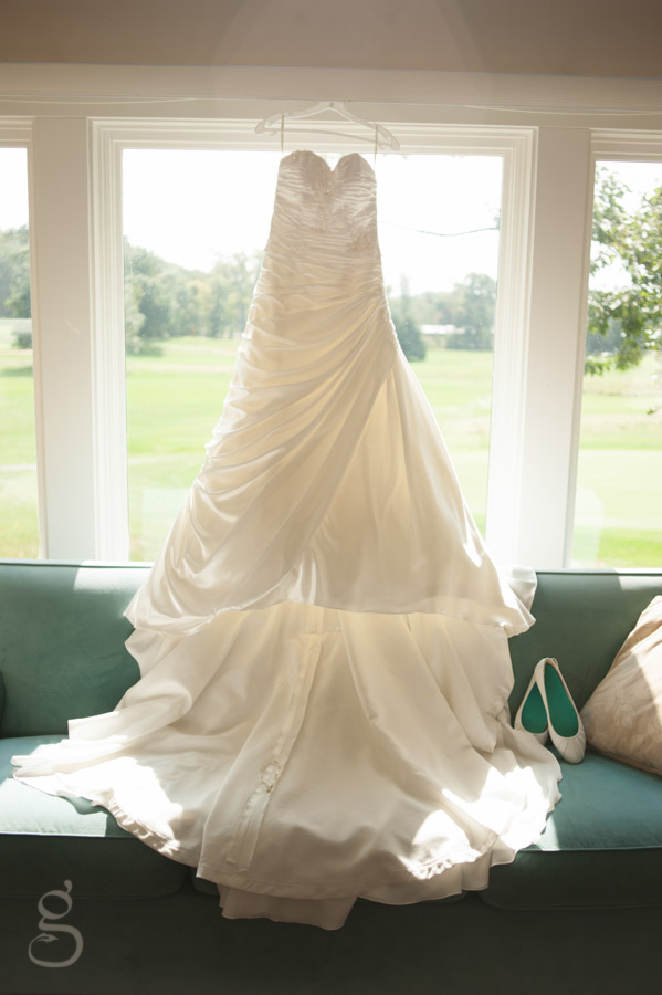 Ruched white wedding gown with ballet flats on a teal couch.