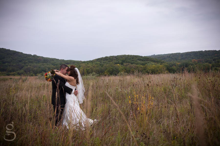 bride and groom in the center of a field of wild flowers.