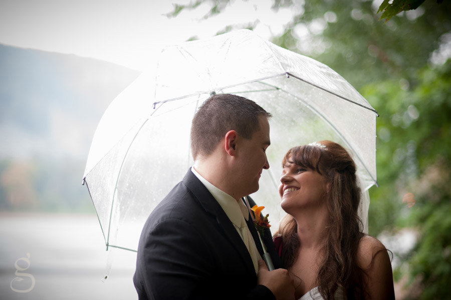 Jacey and Chris smiling at each other on their rainy wedding day with the clear umbrella.