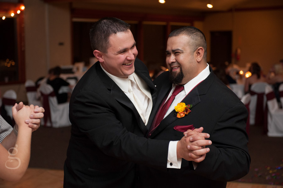 best man and groom laughing and smiling dancing with eath other.