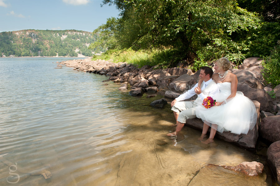 the brave bride and groom with their feet in the lake.