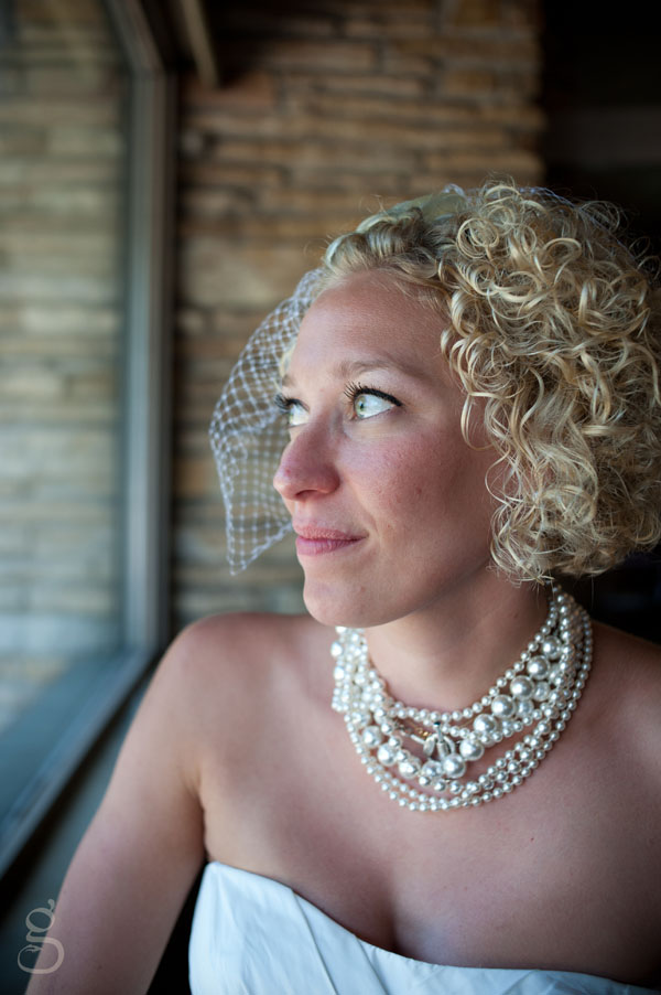 bride and pearls in profile with brick.
