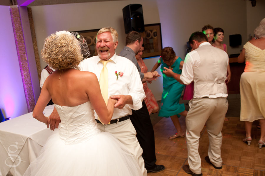 the bride and her father laughing on the dance floor.
