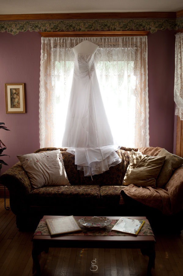 Beautiful princess wedding gown hanging in front of lit window.