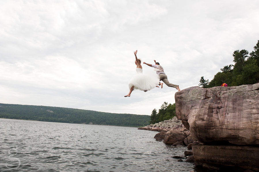 bride and groom jumping into devil's lake.