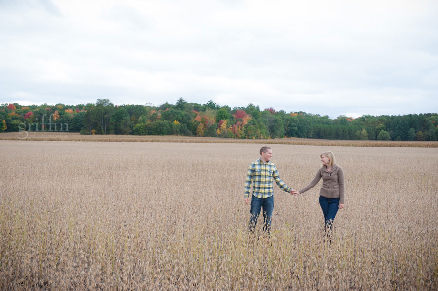couple standing holding hands in a soybean field