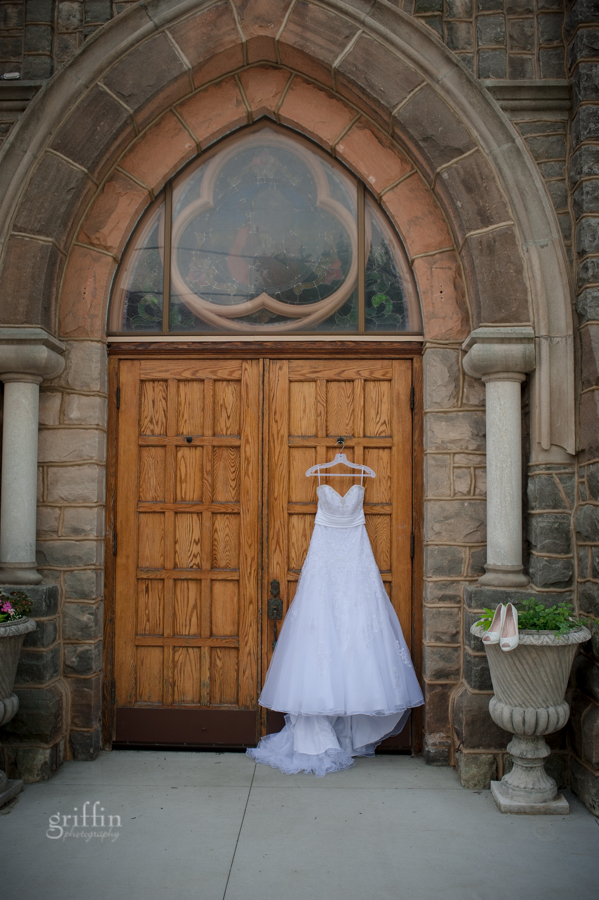 Classic white wedding dress hanging on the wooden church doors.