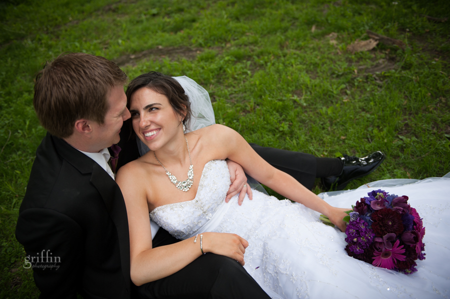 bride and groom sitting on the grass, smiling at each other, feel the love.