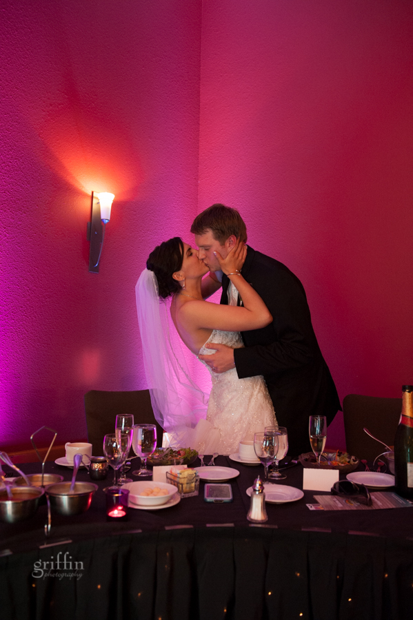 kissing with purple uplighting at the reception.