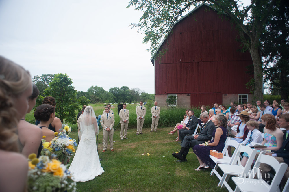 wedding ceremony with rustic barn in background