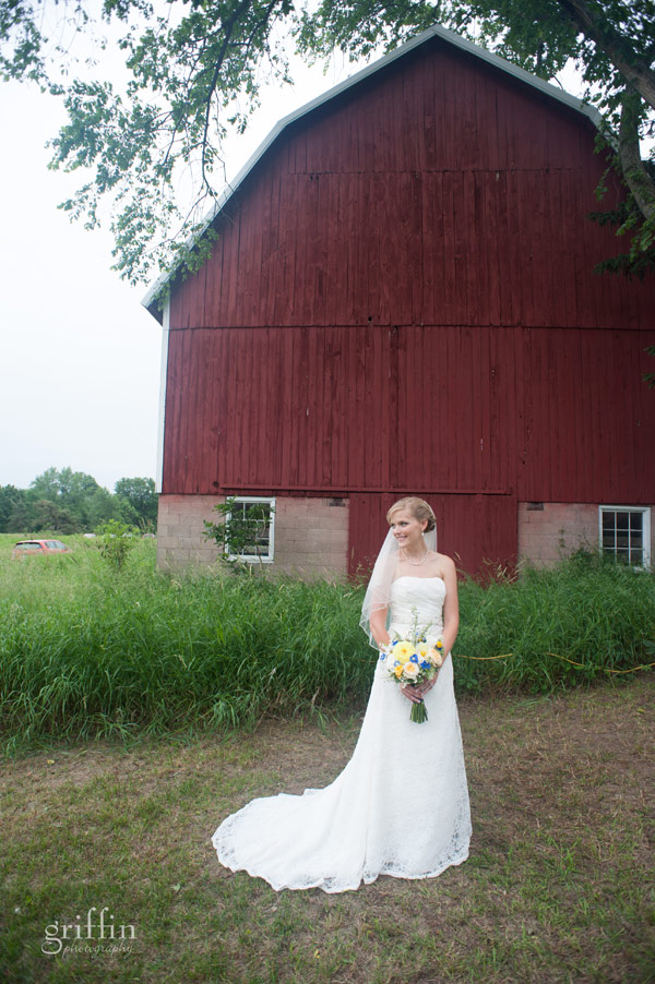 beautiful bride in front the of red family barn.