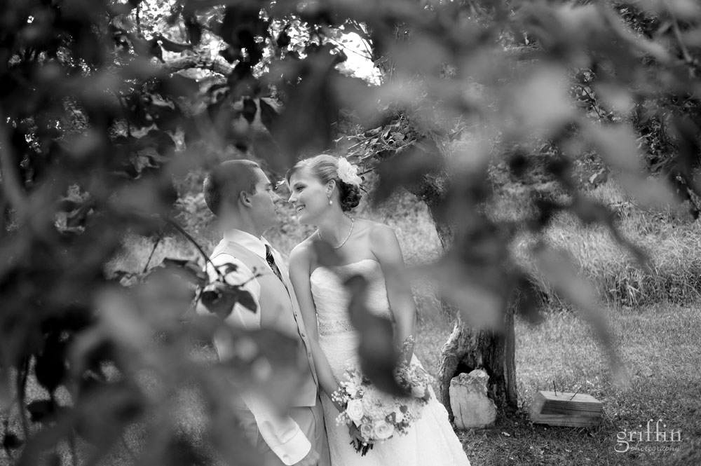 black and white of the wedding couple through the trees