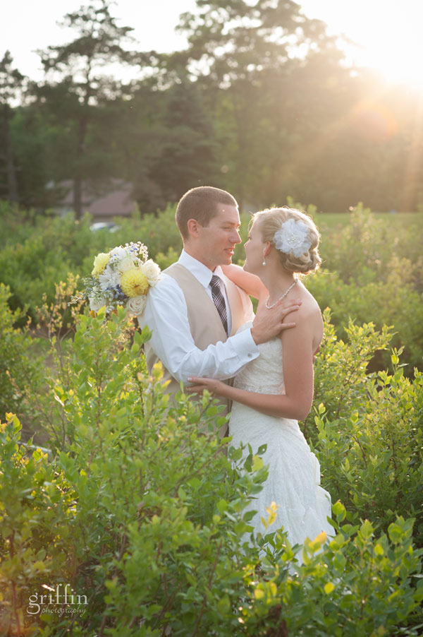 bride and groom in dreamy sunset light and black berry bushes
