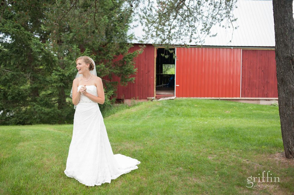 beautiful bride in front of red barn wedding day