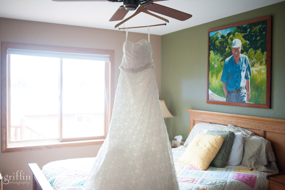 lacy wedding gown hanging in house with handpainted portrait