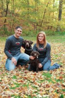 Engaged couple with Chocolate lab puppies posing for the camera in fallen leaves.