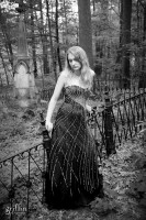 Black and white senior portrait near cemetery with prom dress.