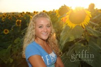 Girl with sun shining through the sunflowers.