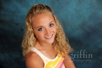 Senior girl smiling up at the camera in the studio.