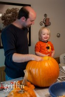 A little smile for the camera while daddy carves his pumpkin.
