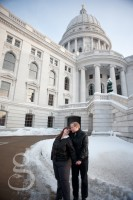 Mand and woman holding hands in front of a snow filled capital building.