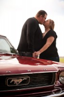 Kissing behind the Mustang during the engagement session.