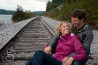 Engaged couple sitting on the railroad tracks looking at each other with love in their eyes.