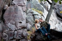 Almost kissing under a tree with huge bluffs in the background.