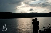 Silhouette of engaged couple hugging with Devil's Lake and storm clouds in the background.