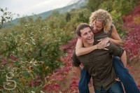 Man giving his fiance a piggy back ride through the wildflowers.