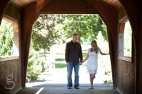 The couple at the end of the covered bridge, looking at each other.