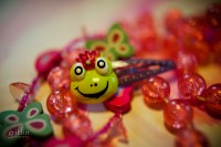 Princess frog hair piece surrounded by hot pink plastic jewelry.