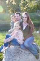 lovely family sitting on a boulder at Pauquette park in Portage.