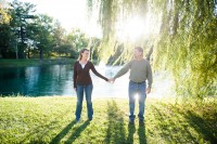 the couple holding hands with the sun shining down.