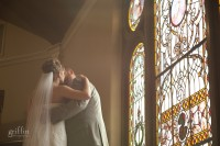 The bride and groom's first look kissing on the steps overlooking the stained glass.