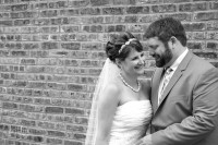 black and white of the bride and groom in front of the brick wall.