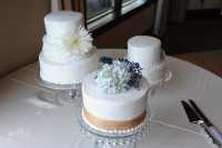 Three wedding cakes with fresh flowers and ribbon on the white cake table, very simple elegant design.