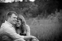 black and white shot of engaged couple laughing in a field at devil's lake in Baraboo wi.